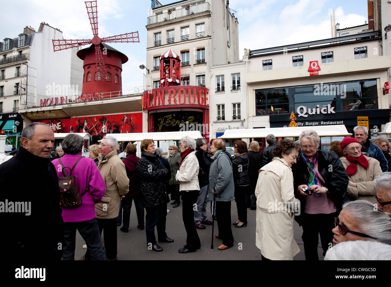 a croud of elderly tourists outside The Moulin Rouge, Paris, France - Stock Image