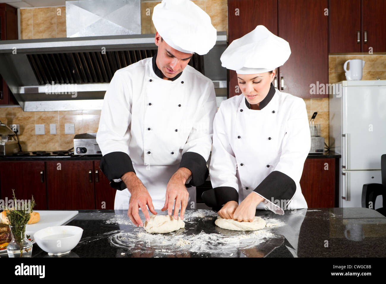 chefs making dough in kitchen - Stock Image