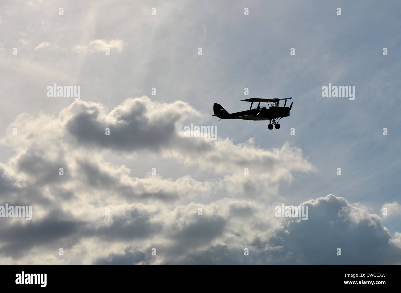 Silhouetted bi-plane against a cloudy sky - Stock Image