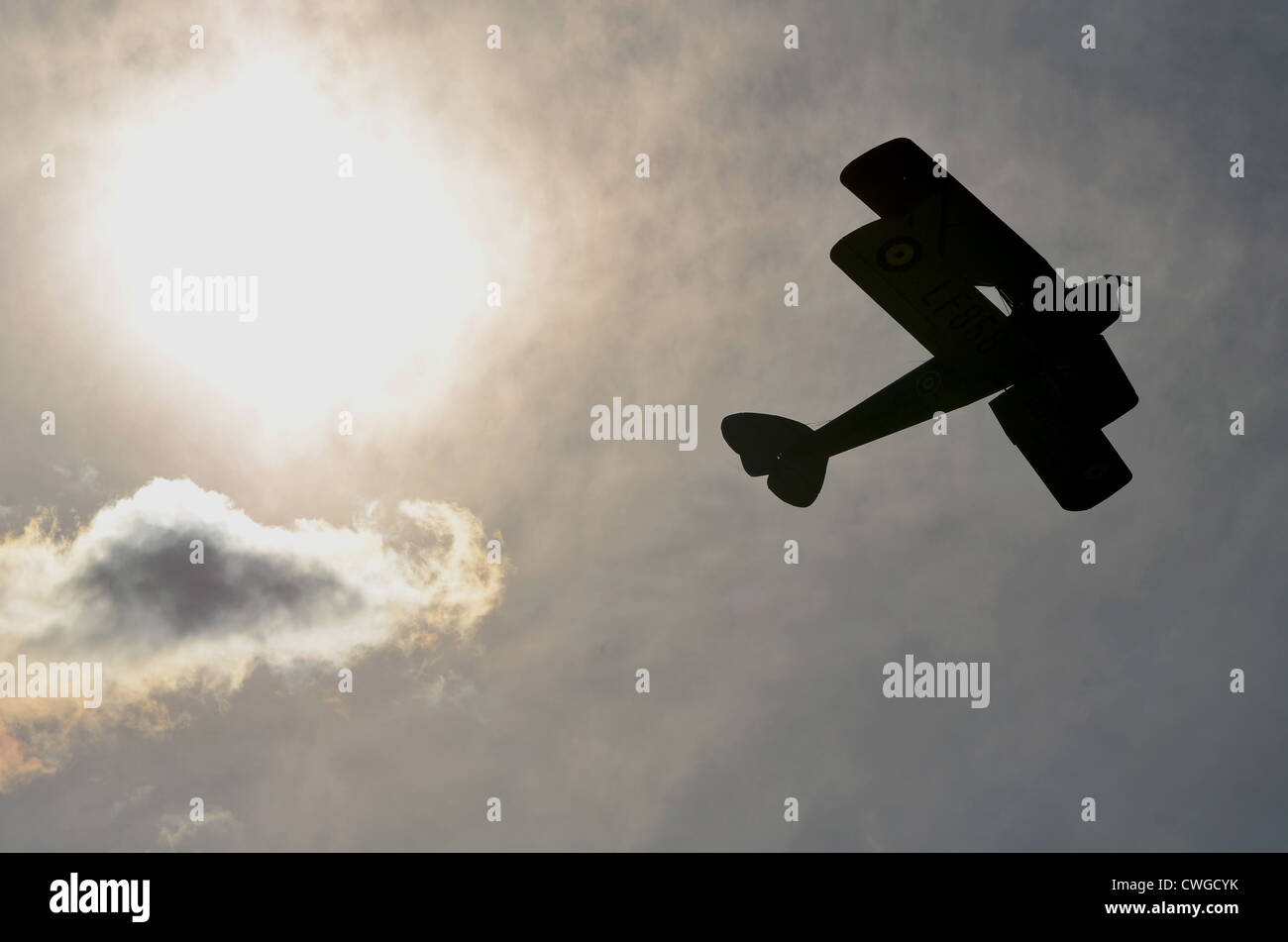Silhouette of a bi-plane flying across the sky. Stock Photo