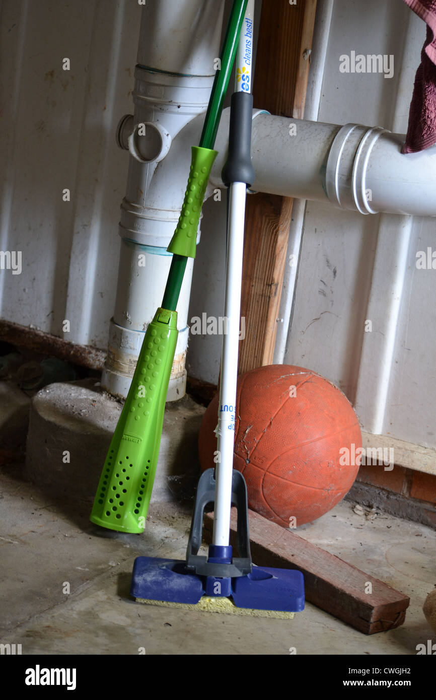Old mops resting against pipes in garage. Also featuring a very old basketball - Stock Image