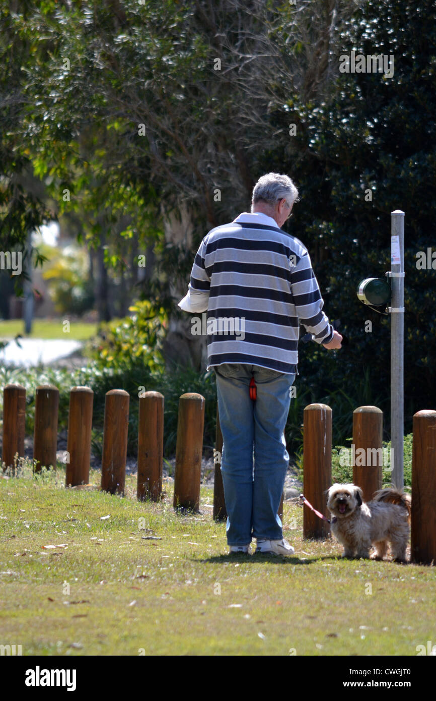 Man taking a doggie doo bag from the dispenser while out with his dog - Stock Image
