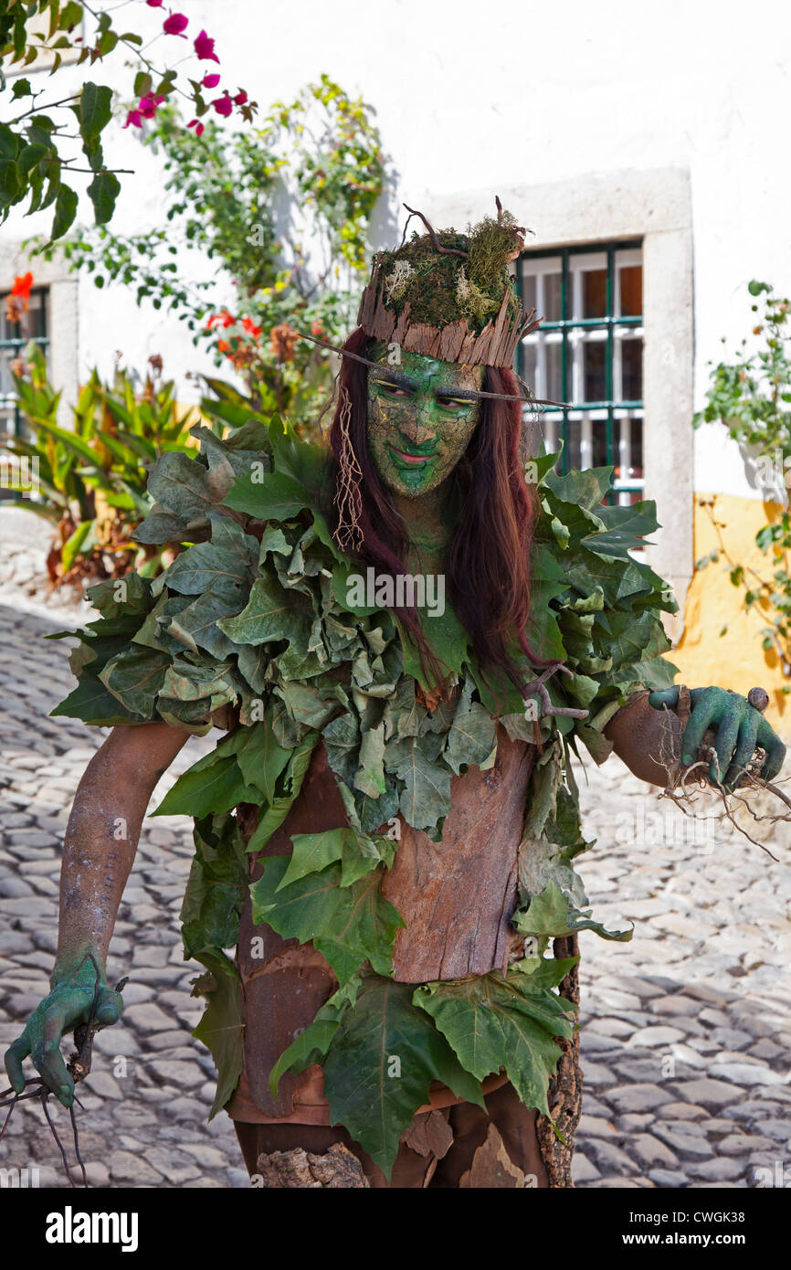 Live statue street performance artist in a reenactment of a Medieval Fair in Óbidos, Portugal. - Stock Image