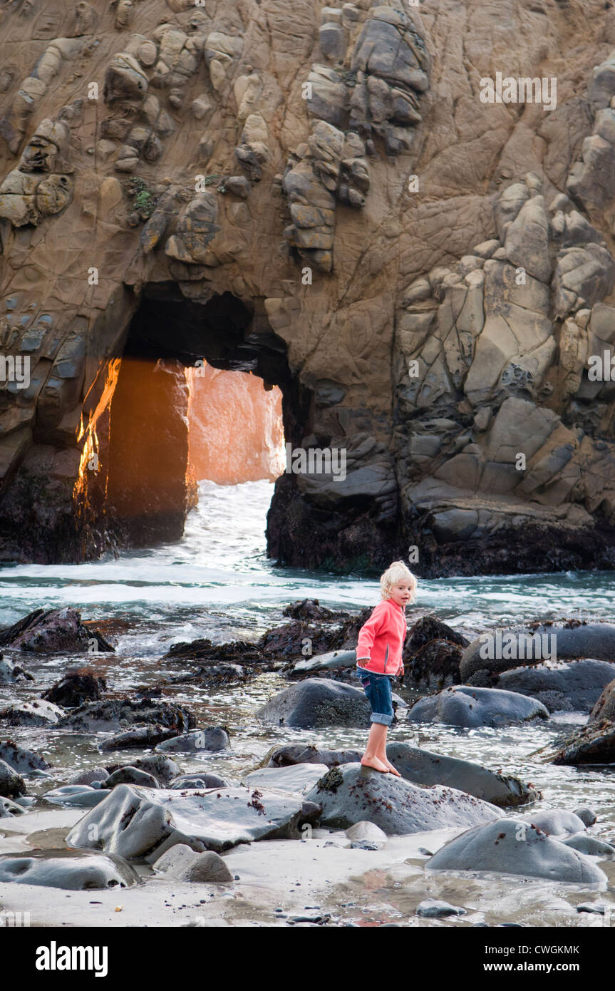 A young girl playing in the ocean near a blow hole, Big Sur, California. - Stock Image