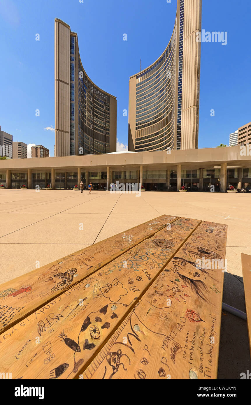 Graffiti on a table in Nathan Phillips Square with the Toronto City Hall in the background. Ontario, Canada. - Stock Image