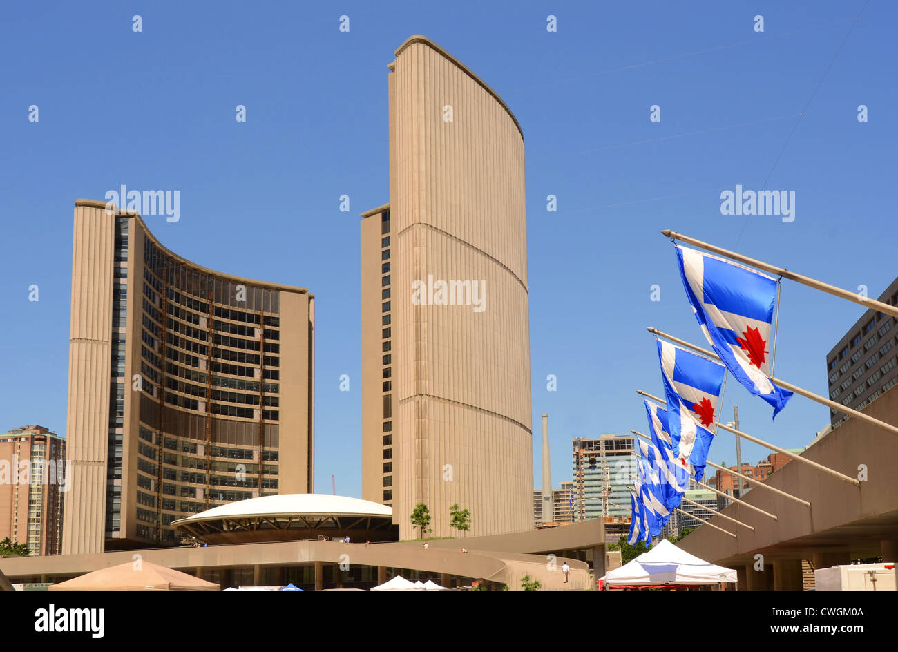 The blue and red flags of Toronto flying outside the City Hall at Nathan Phillips Square,Toronto, Ontario, Canada. - Stock Image