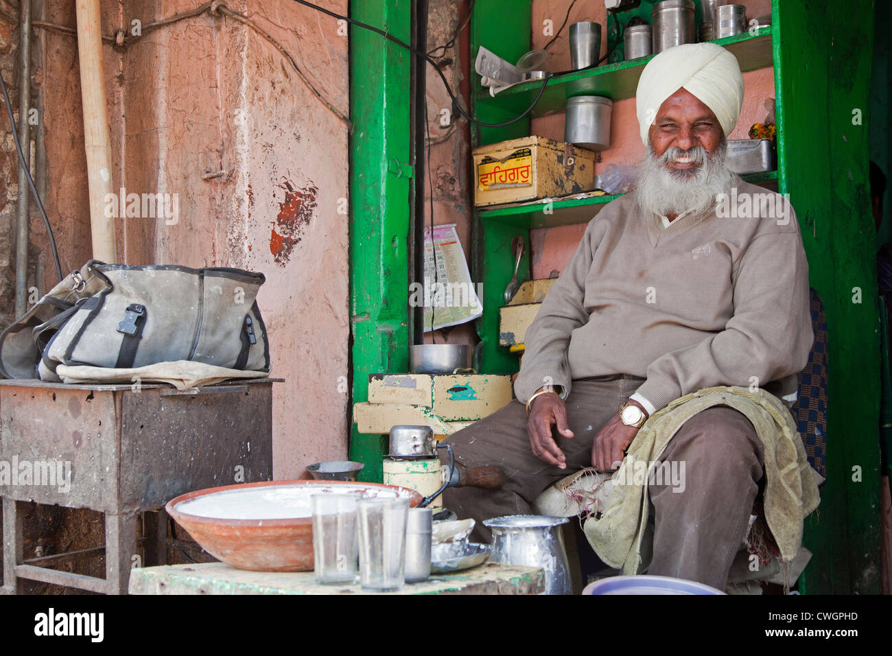 Sikh shopkeeper wearing turban selling lassi, traditional yogurt-based drink, in Jaipur, Rajasthan, India - Stock Image