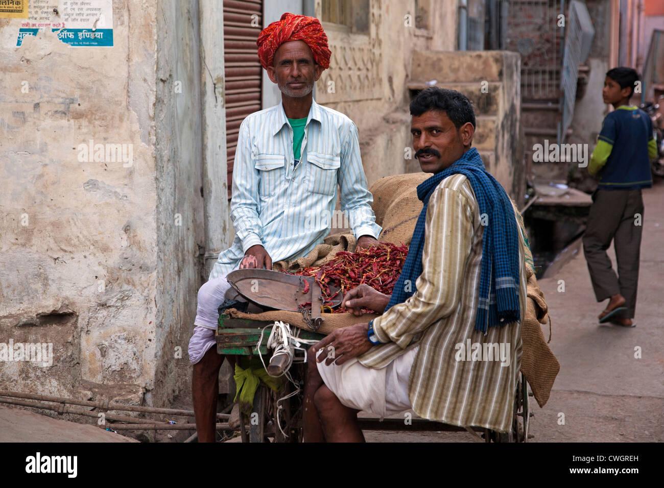 Men selling red peppers on street in Bundi, Rajasthan, India - Stock Image