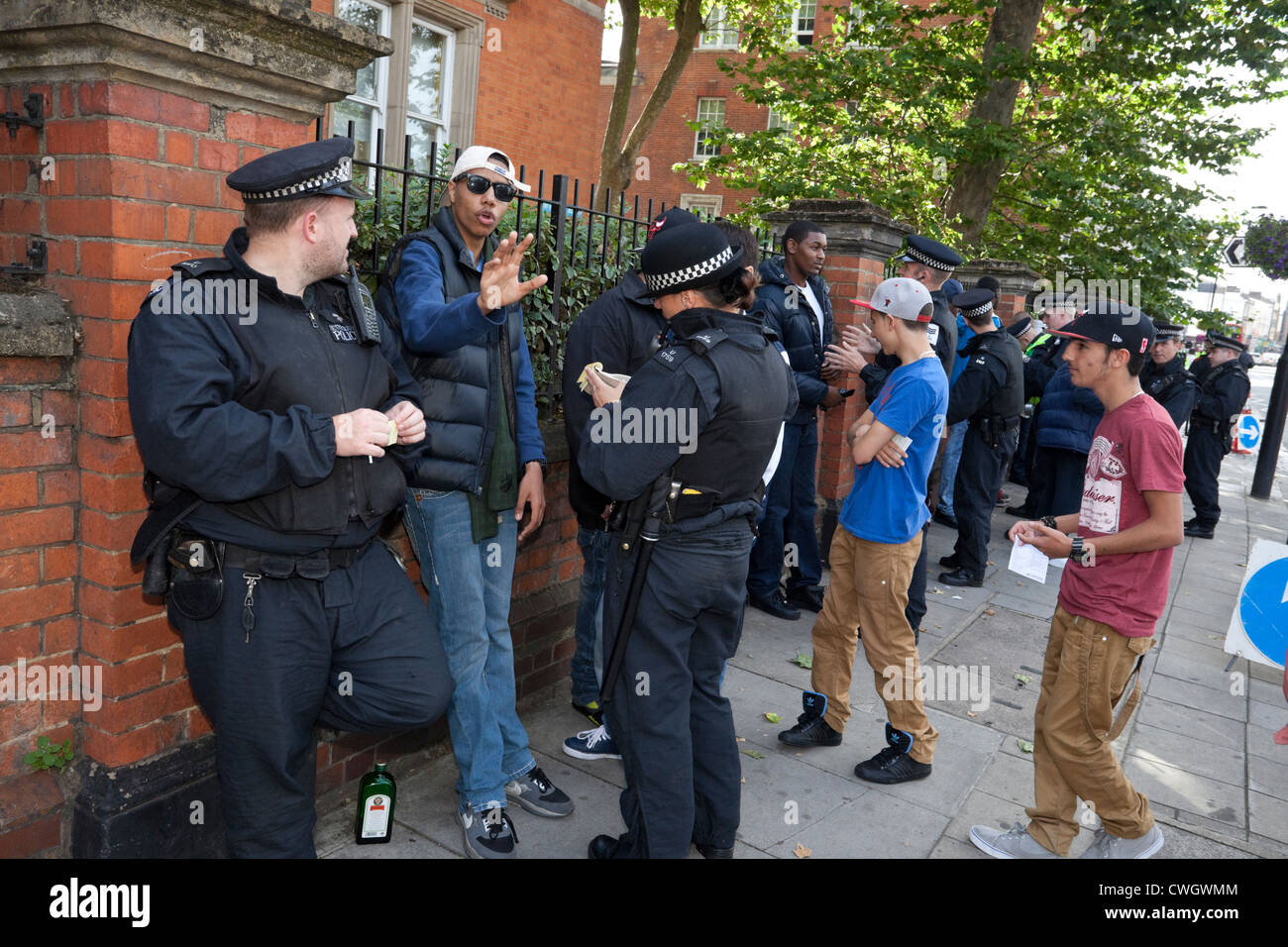 Metropolitan police officers stop and search a group of youths at the Notting Hill Carnival 2012, London, England, - Stock Image
