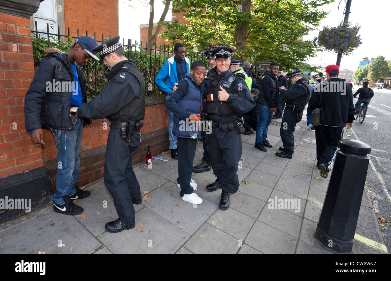 Metropolitan police officers stop and search a group of black youths at the Notting Hill Carnival 2012, London, - Stock Image