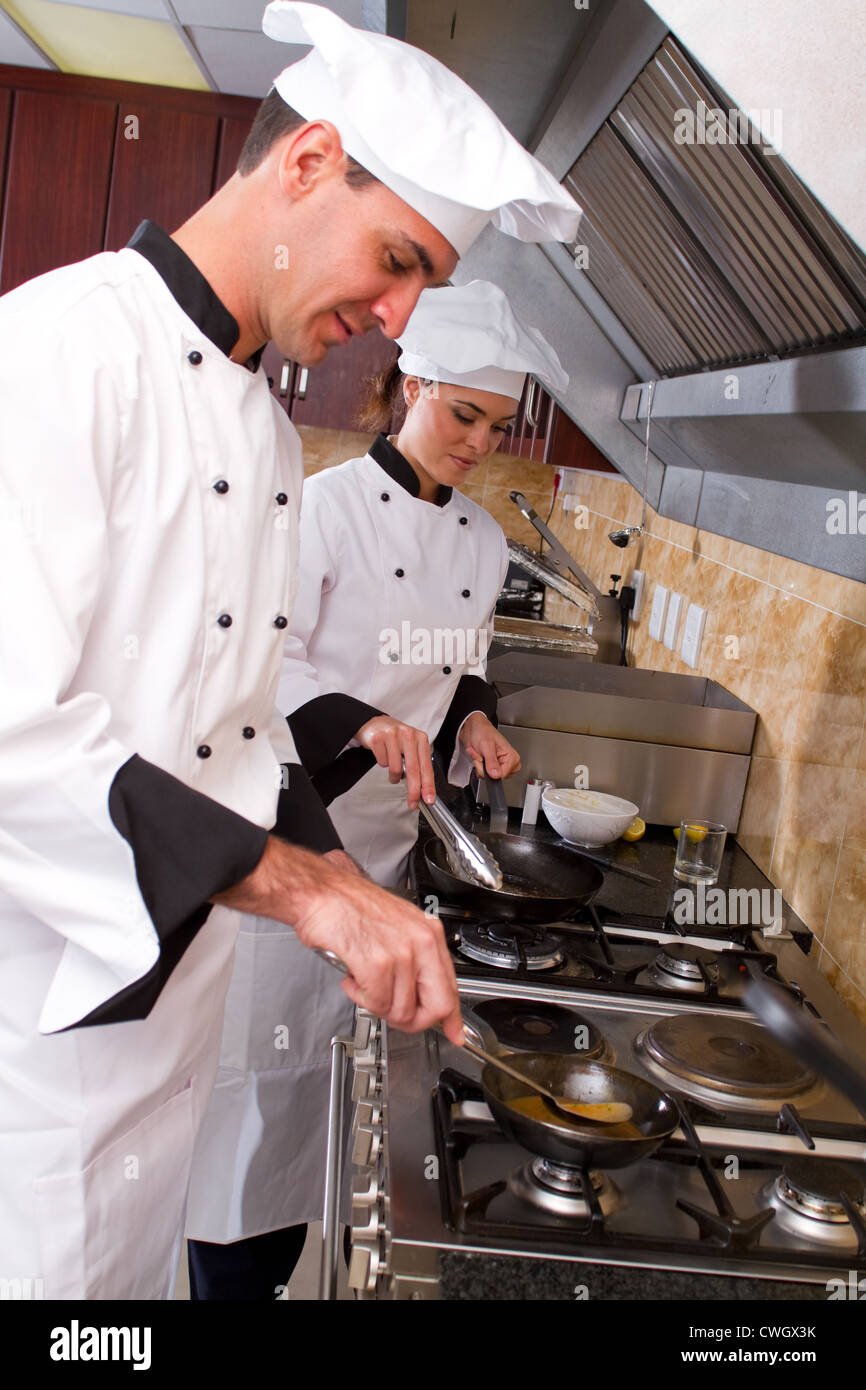 two young professional chefs cooking in kitchen - Stock Image