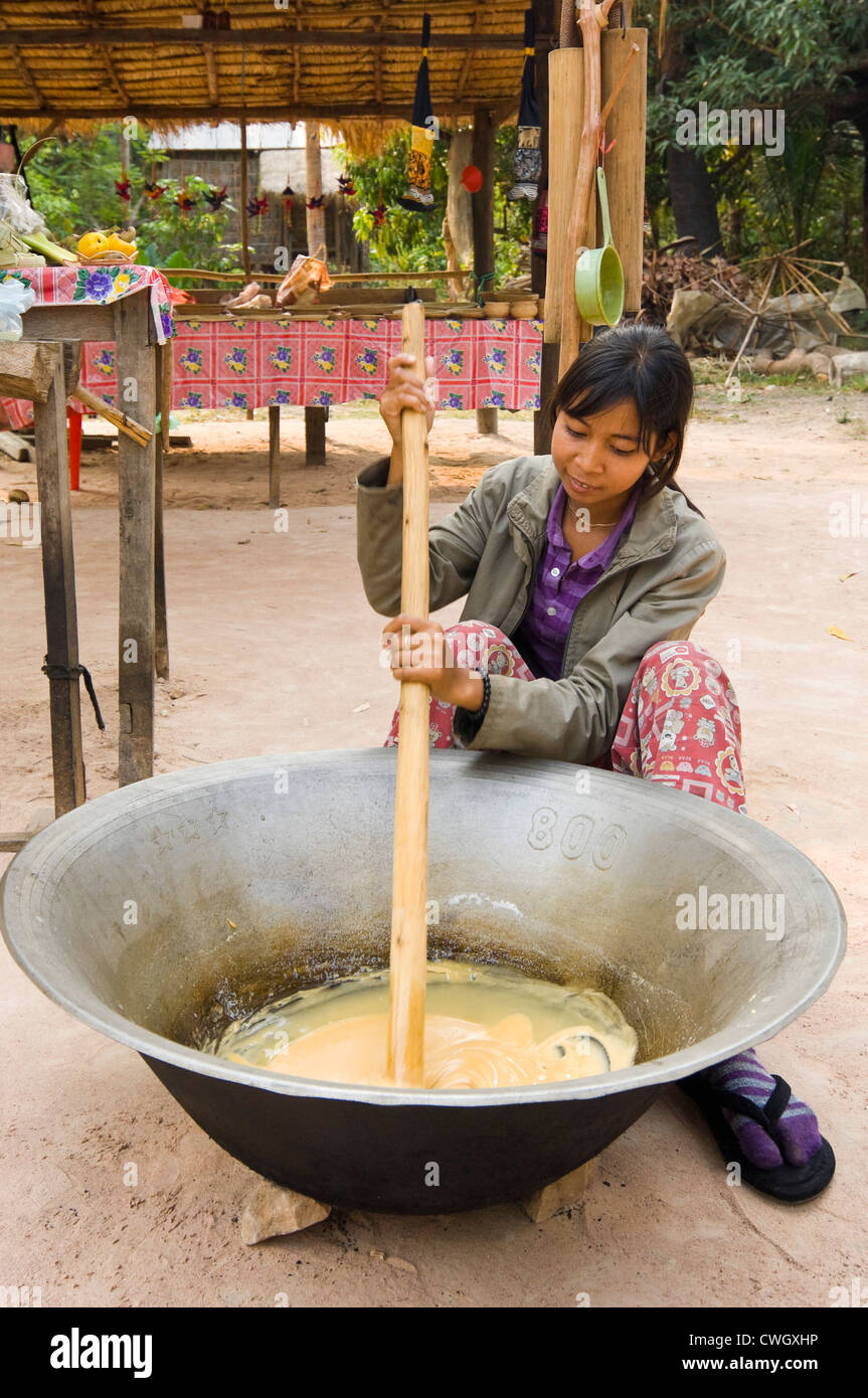 Vertical portrait of a Cambodian woman making traditional palm sugar sweets also used widely in Cambodian and Asian - Stock Image