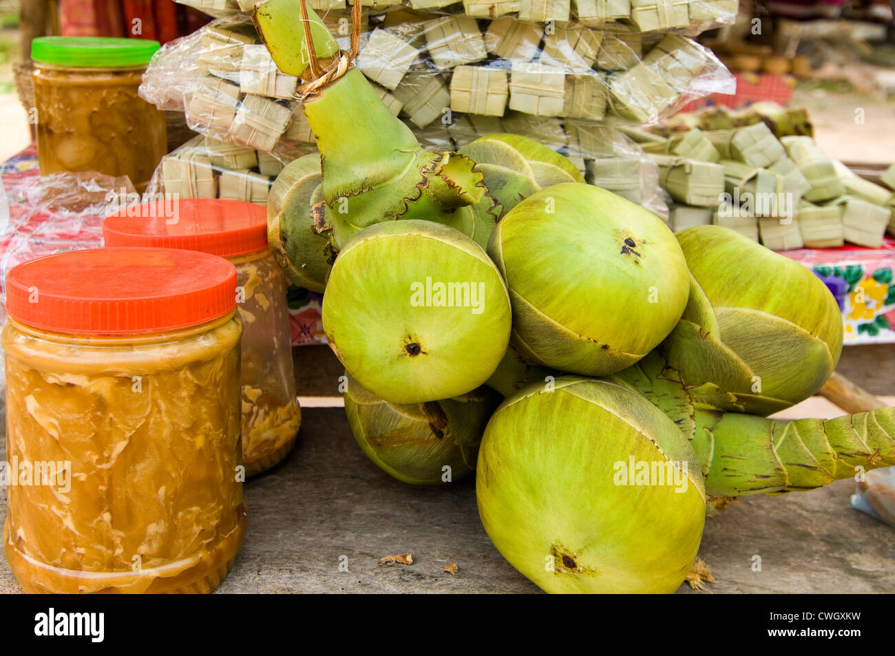 Horizontal close up of tubs of palm sugar, fresh coconuts and the tubes of prepared palm sugar sweets ready to sell - Stock Image