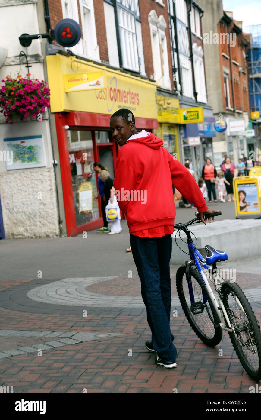 Afro Caribbean Man Walking With Bicycle Down The Street Sutton Surrey England - Stock Image