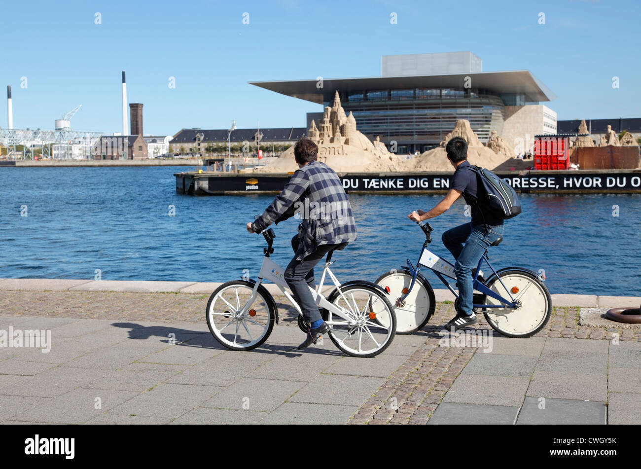 Two male tourists cycling along the quayside at Larsens Plads on the free city bikes looking at sand sculptures - Stock Image