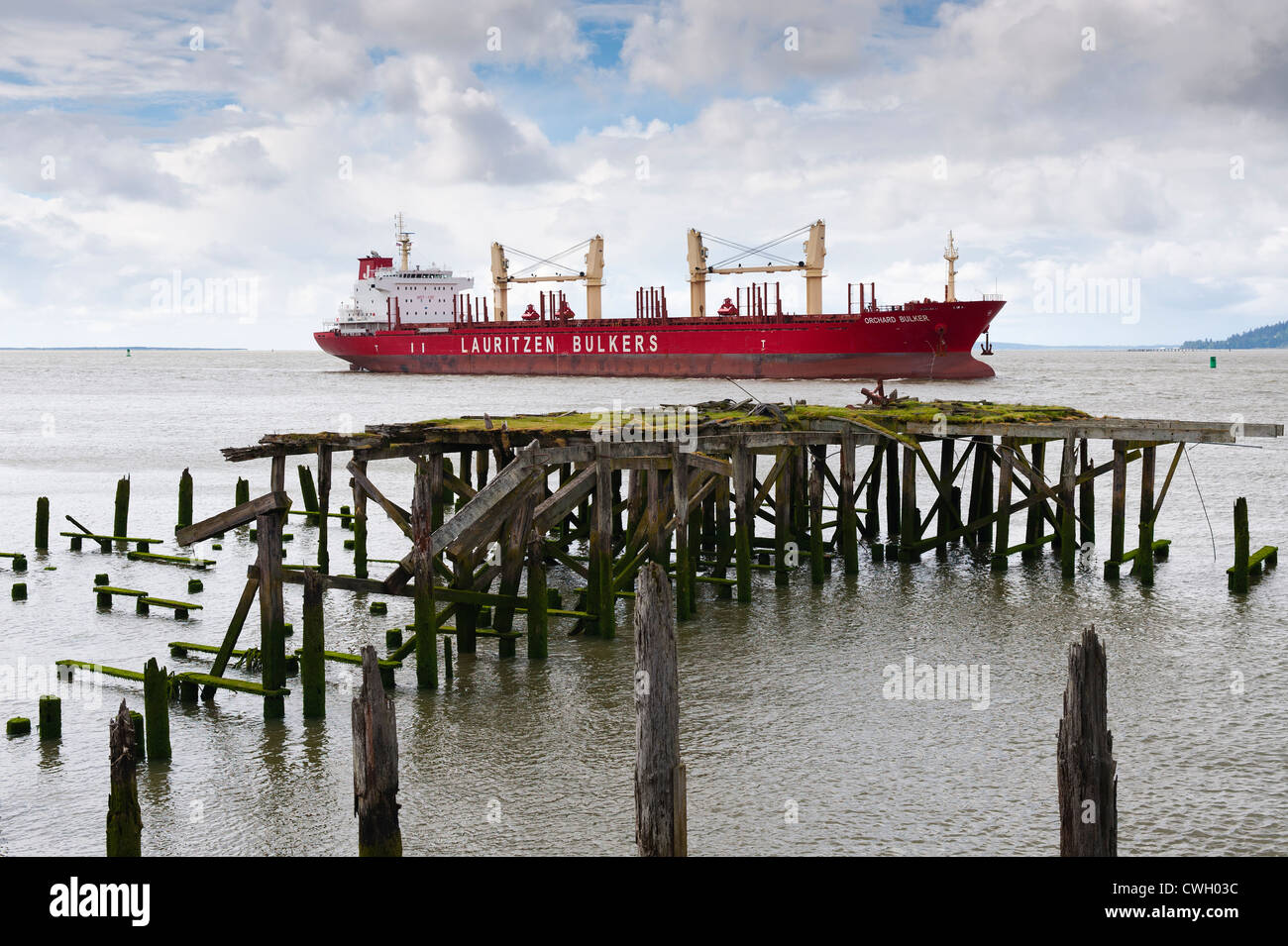 Cargo ship Orchard Bulker of Lauritzen Bulkers shipping line steams upriver in the navigable shipping channel on Stock Photo