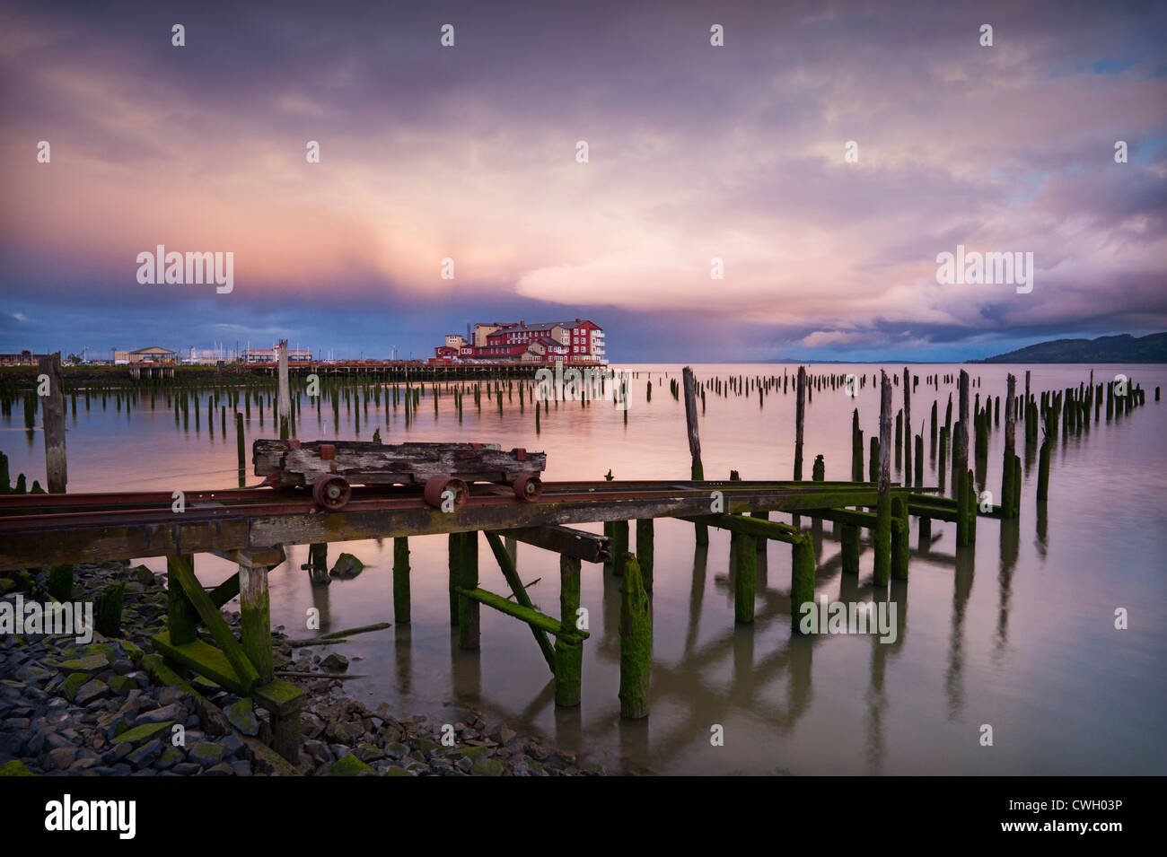 Spectacular clouds and sunrise light reflected in the Columbia River with hundred-year old pilings and the Cannery - Stock Image