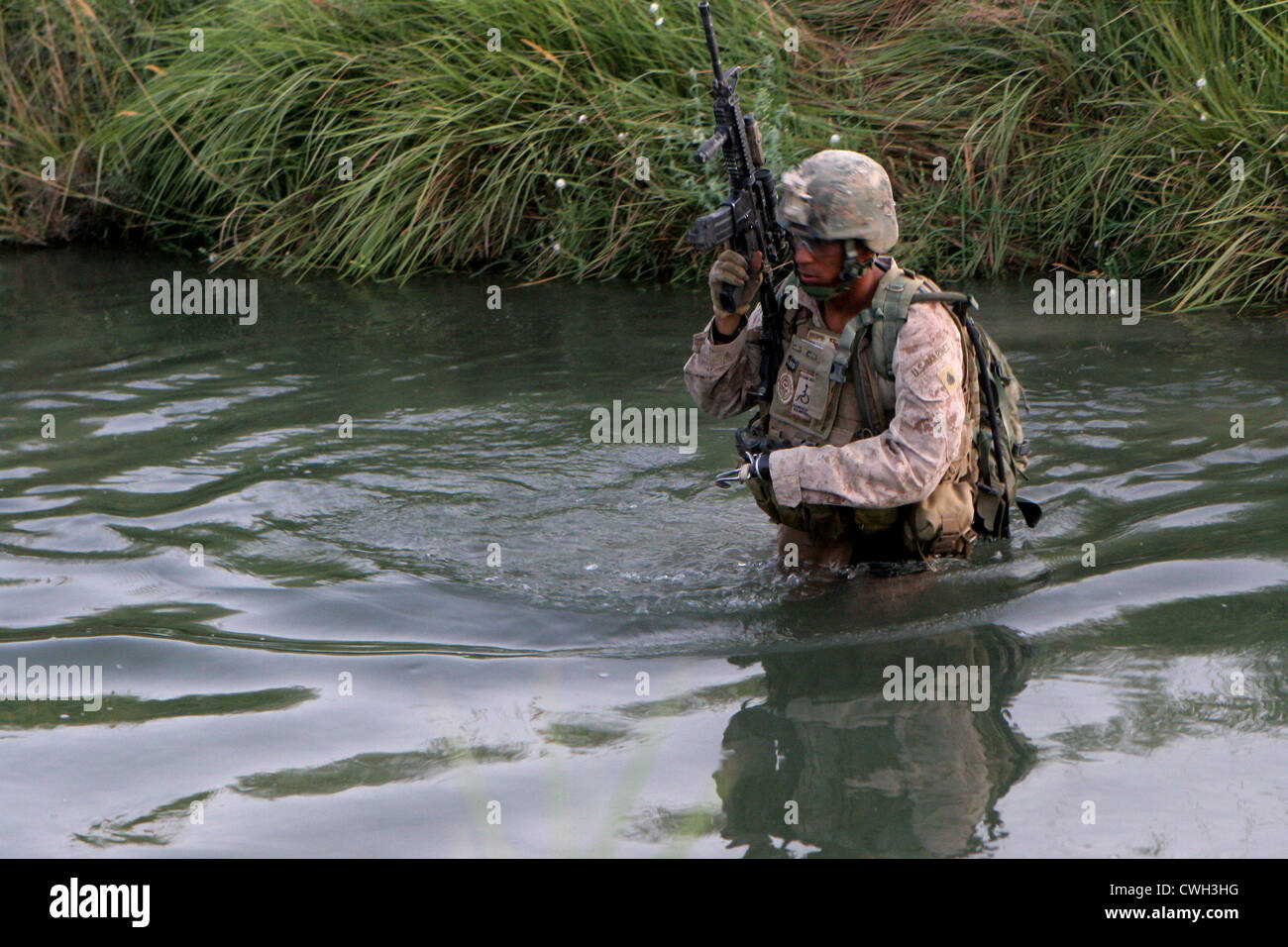 US Marine Sgt. Ricardo Ramirez wades through an irrigation canal to move into a night observation post in Sangin, - Stock Image