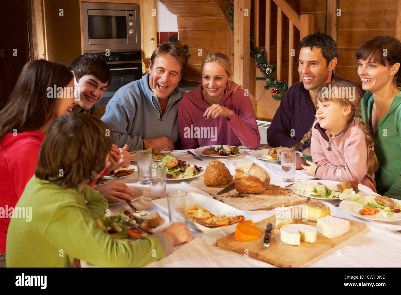 Two Familes Enjoying Meal In Alpine Chalet Together - Stock Image