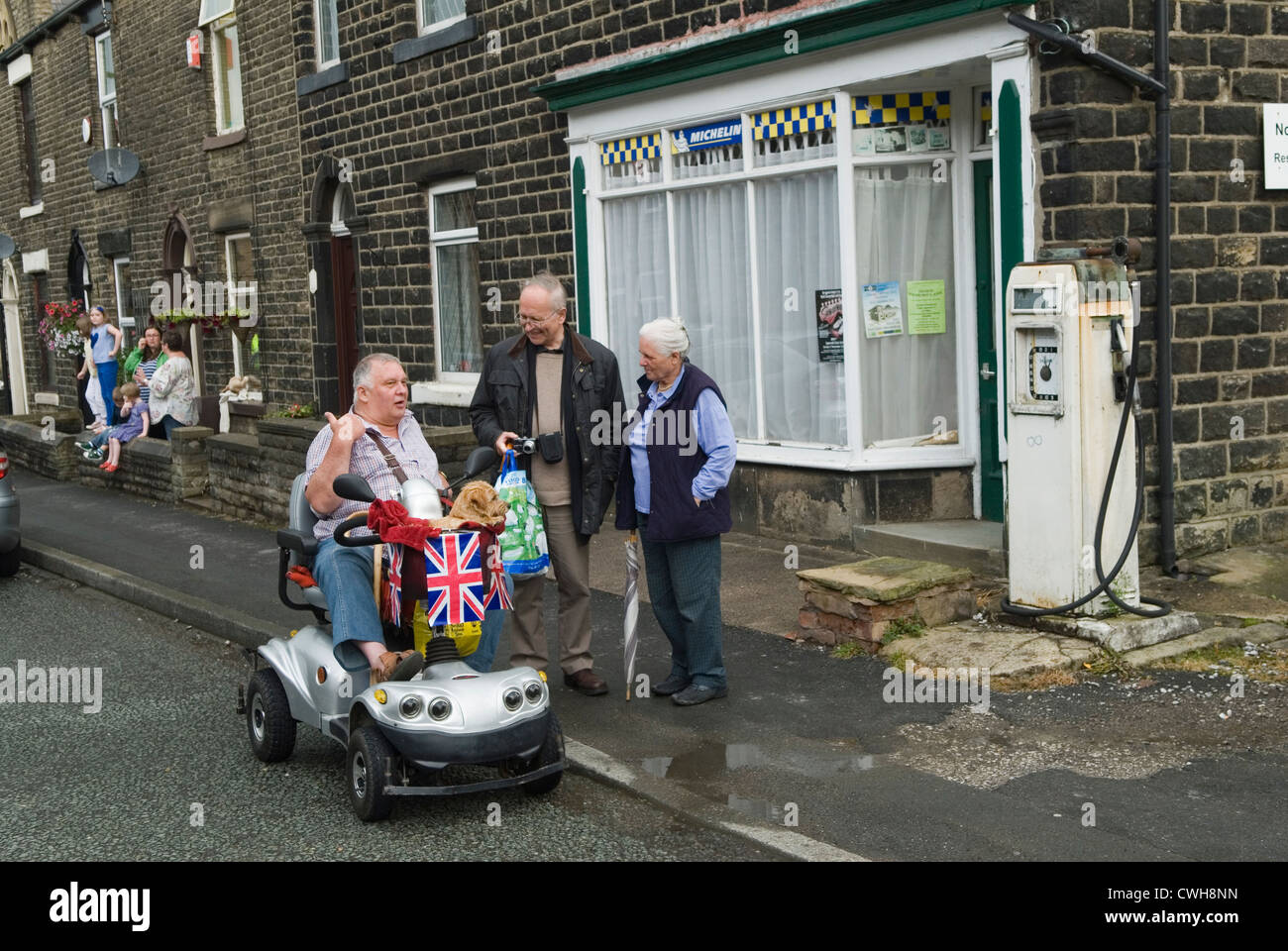 Mobility vehicle disabled man with dog using a mobility motorised decorated scooter talking with friends  UK HOMER - Stock Image