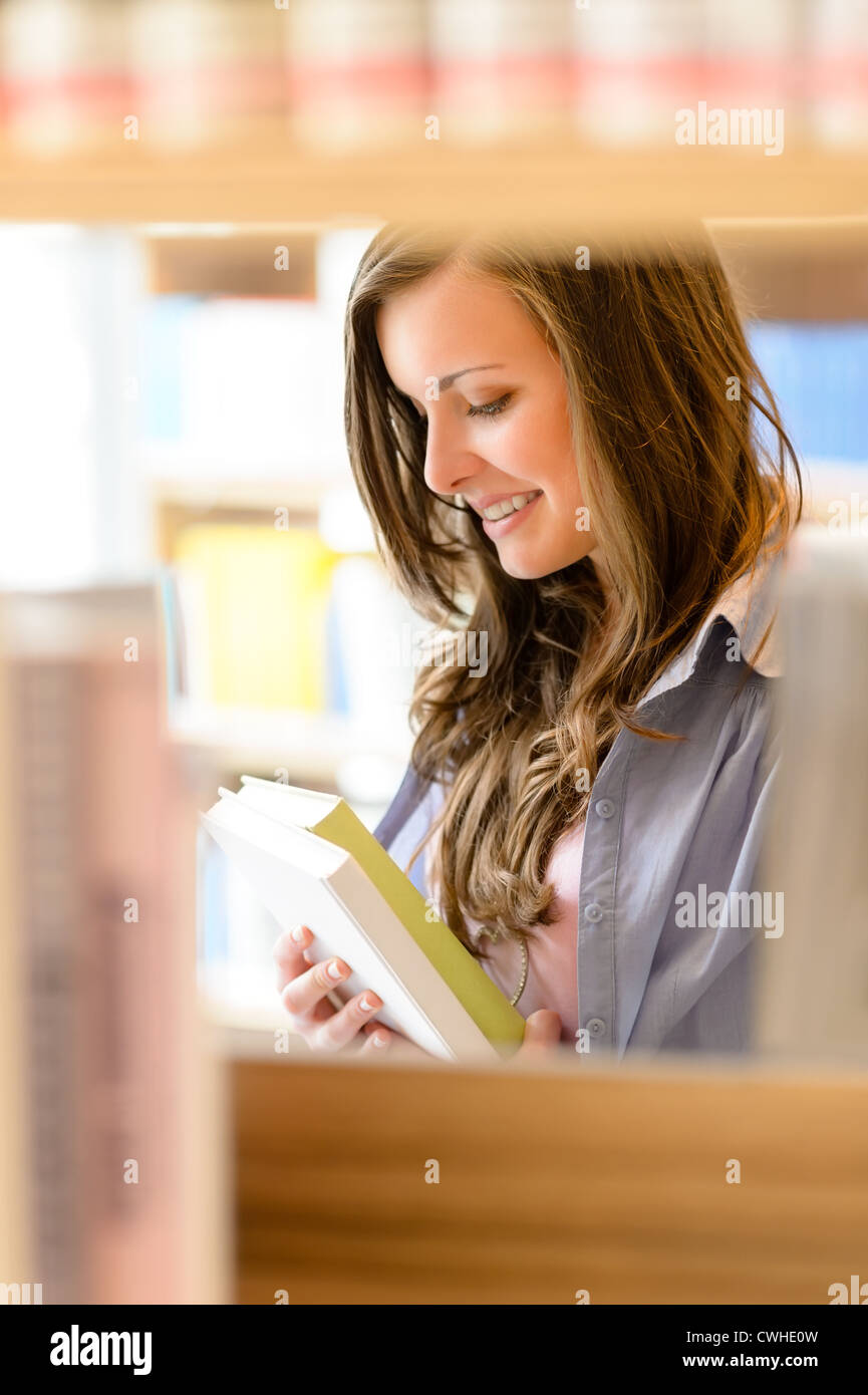 Young student woman reading book among library shelves - Stock Image