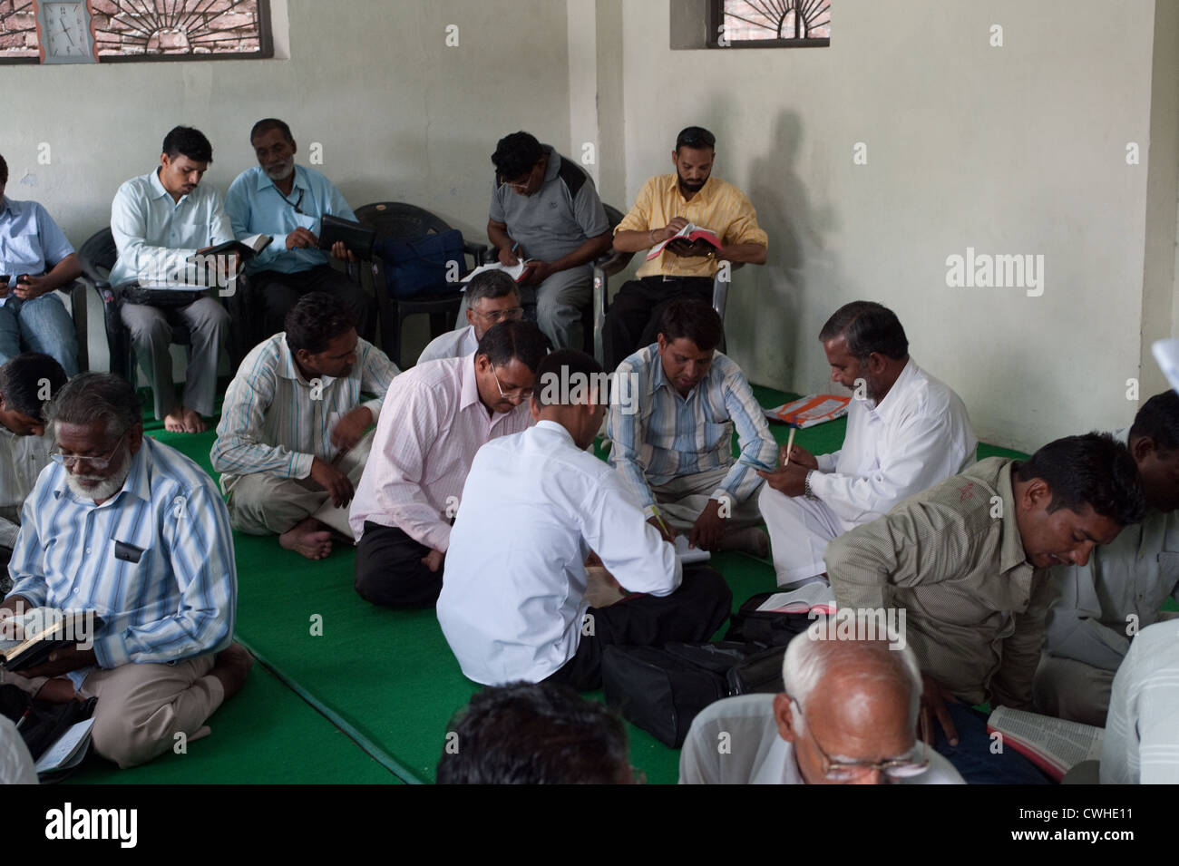 Punjab India Christian pastors studying the Bible in a class setting.  Pastors sitting on the floor and in chairs - Stock Image