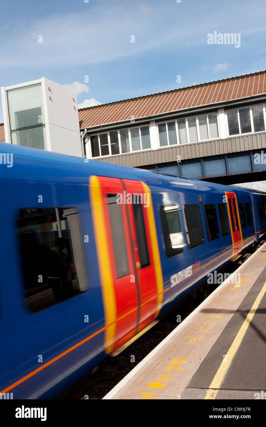 Carriages of a passenger train in South West Trains livery speeding through Clapham Junction station, England. - Stock Image