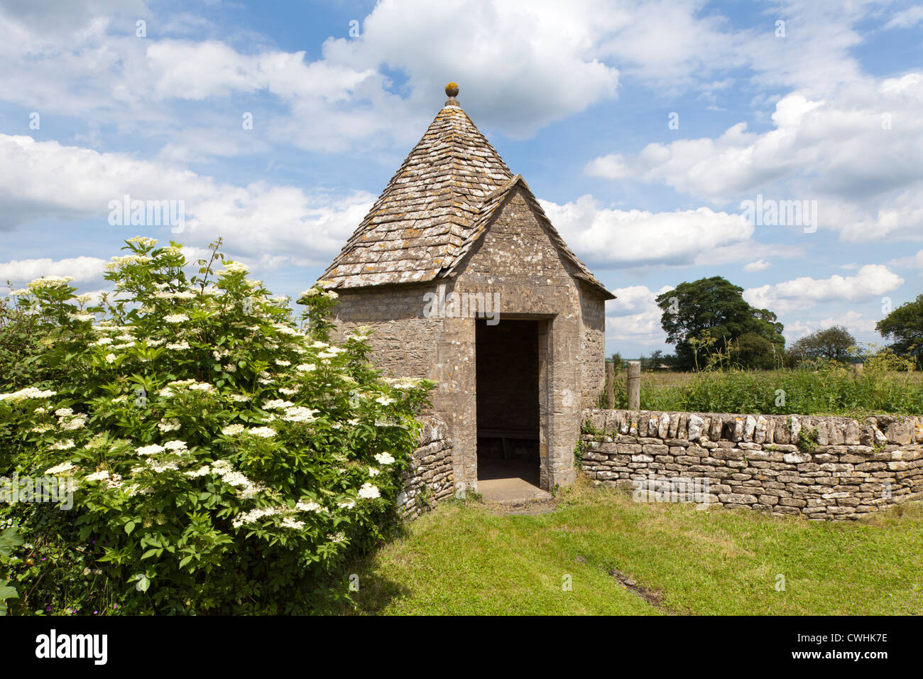 A delightfully quirky octagonal bus shelter built of Cotswold stone in the Cotswold village of Farmington, Gloucestershire, - Stock Image