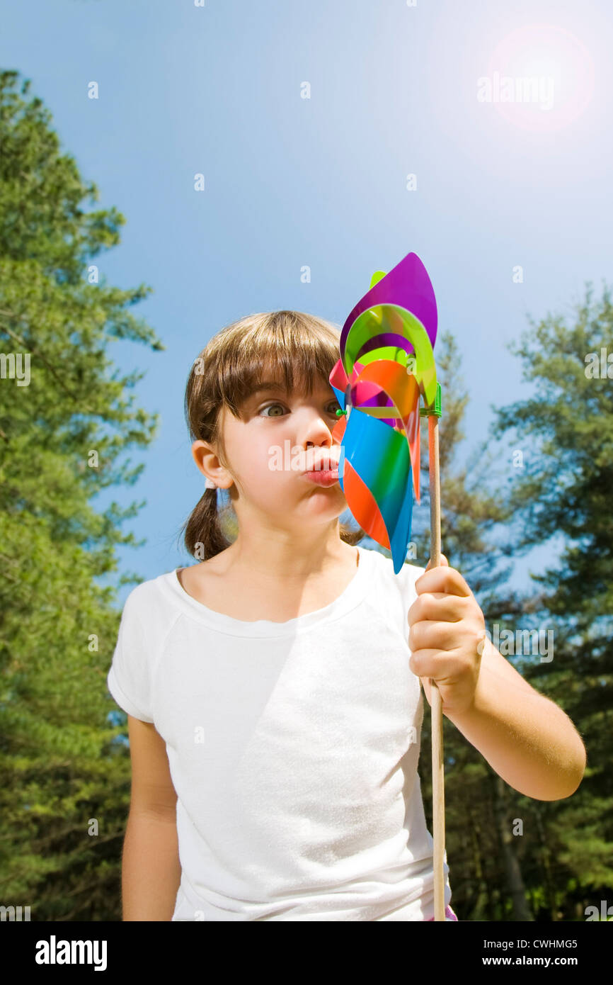 girl,pinwheel,blowing - Stock Image