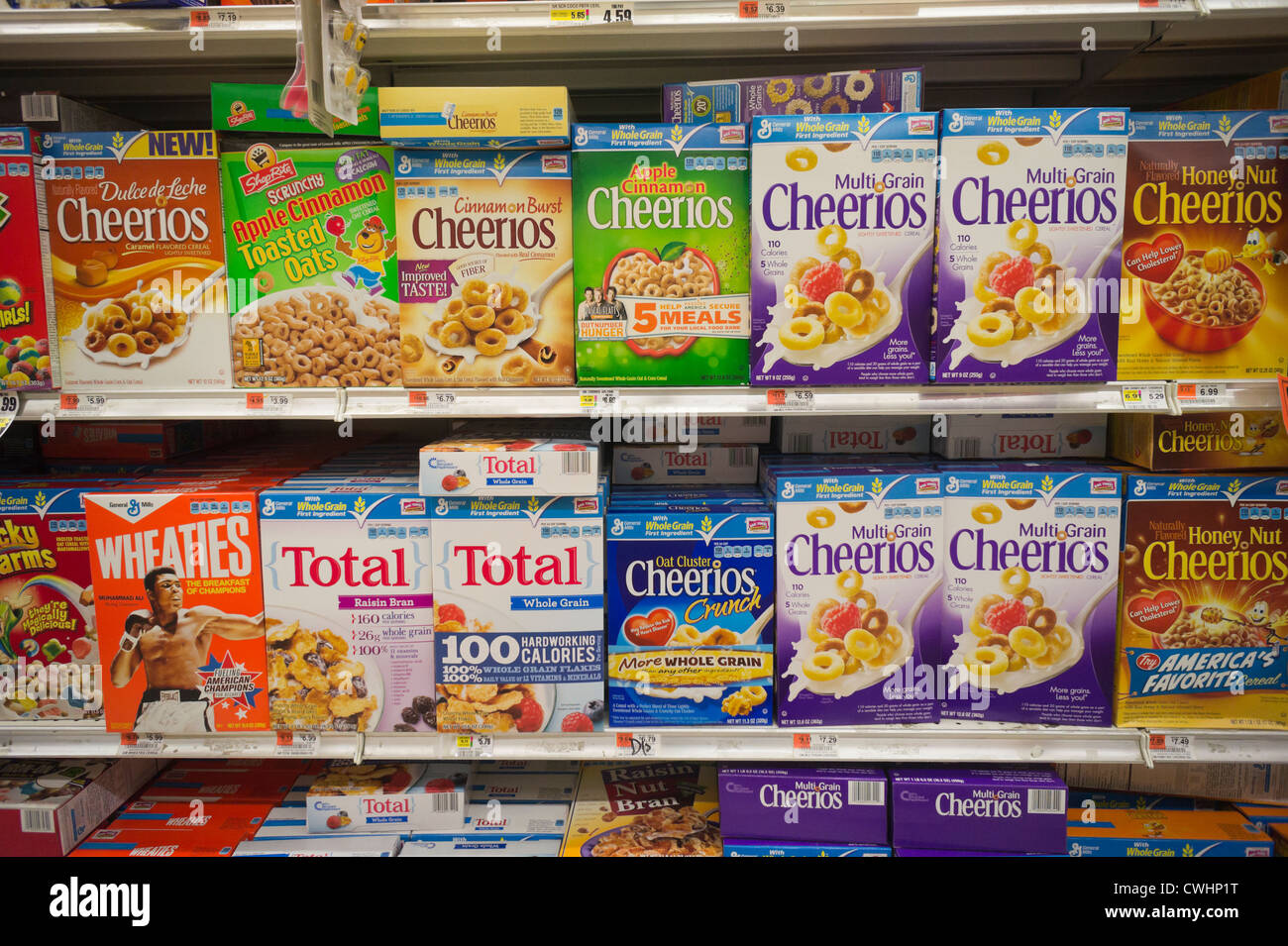Boxes of General Mills breakfast cereals mixed in with house brand similars on supermarket shelves - Stock Image