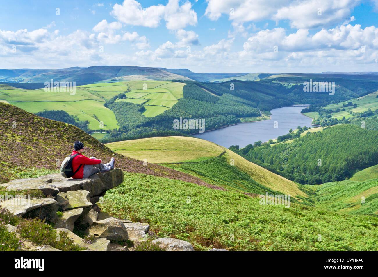 Hiker sat on Whinstone Lee Tor Derwent moor above Ladybower reservoir Derbyshire Peak District national park Derbyshire - Stock Image