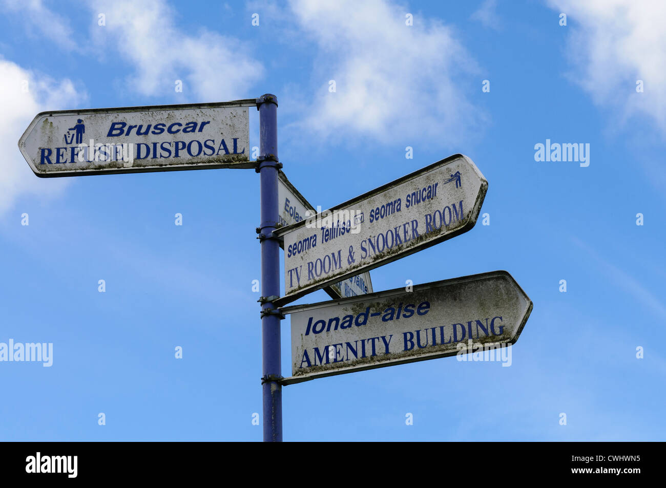 Bilingual signs in Irish Gaelic and English at an abandoned adventure centre/outdoor pursuits hotel. - Stock Image