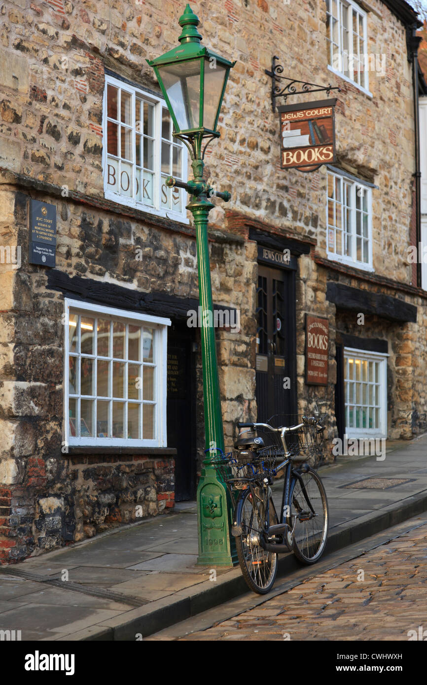 Bicycle by a leaning lamppost outside an old book shop in historic quarter of city of Lincoln, Lincolnshire, England, Stock Photo