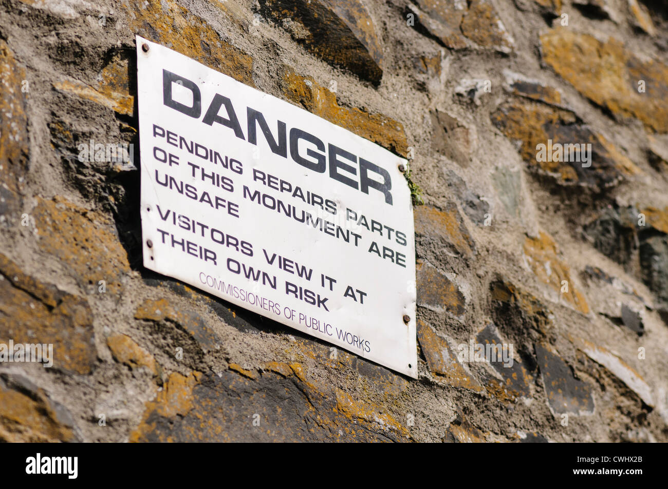 Sign warning visitors that a monument is unsafe, and advising them that they view at their own risk. Stock Photo