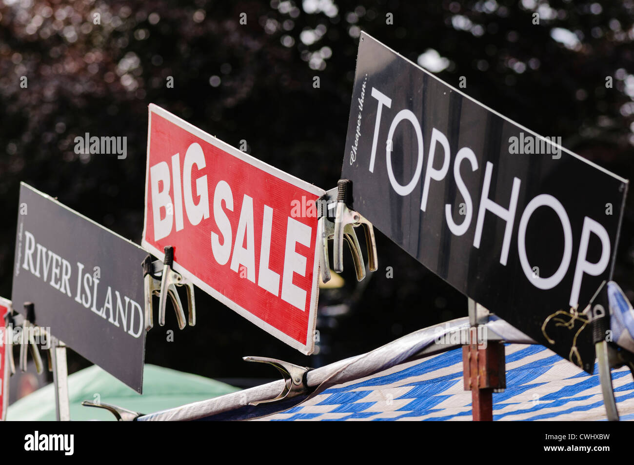 Signs advertising counterfeit products from River Island and Top shop at a market stall Stock Photo