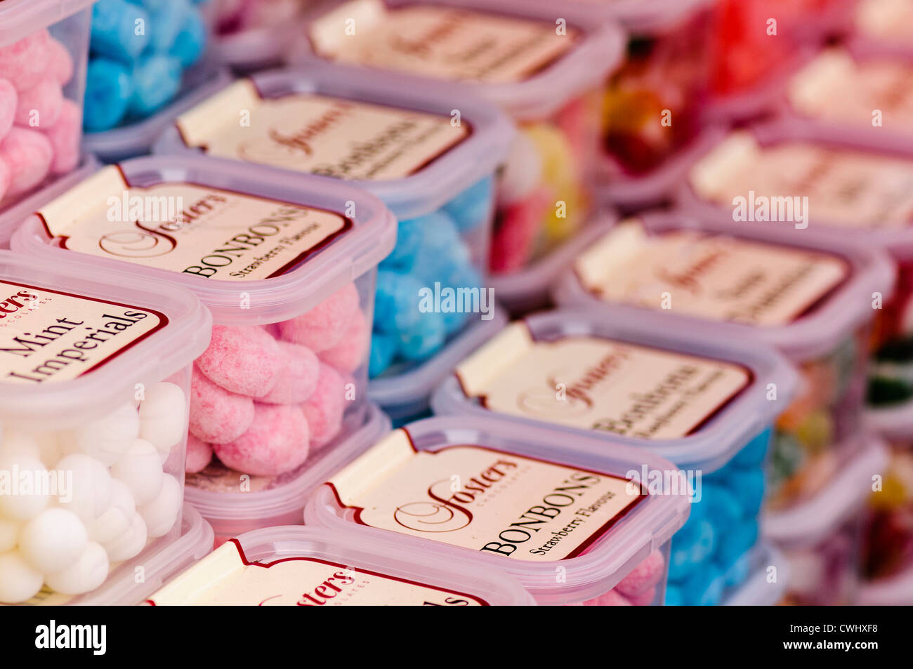 Tubs of Foster's sweets, including bonbons and mint imperials, on sale at a market stall - Stock Image