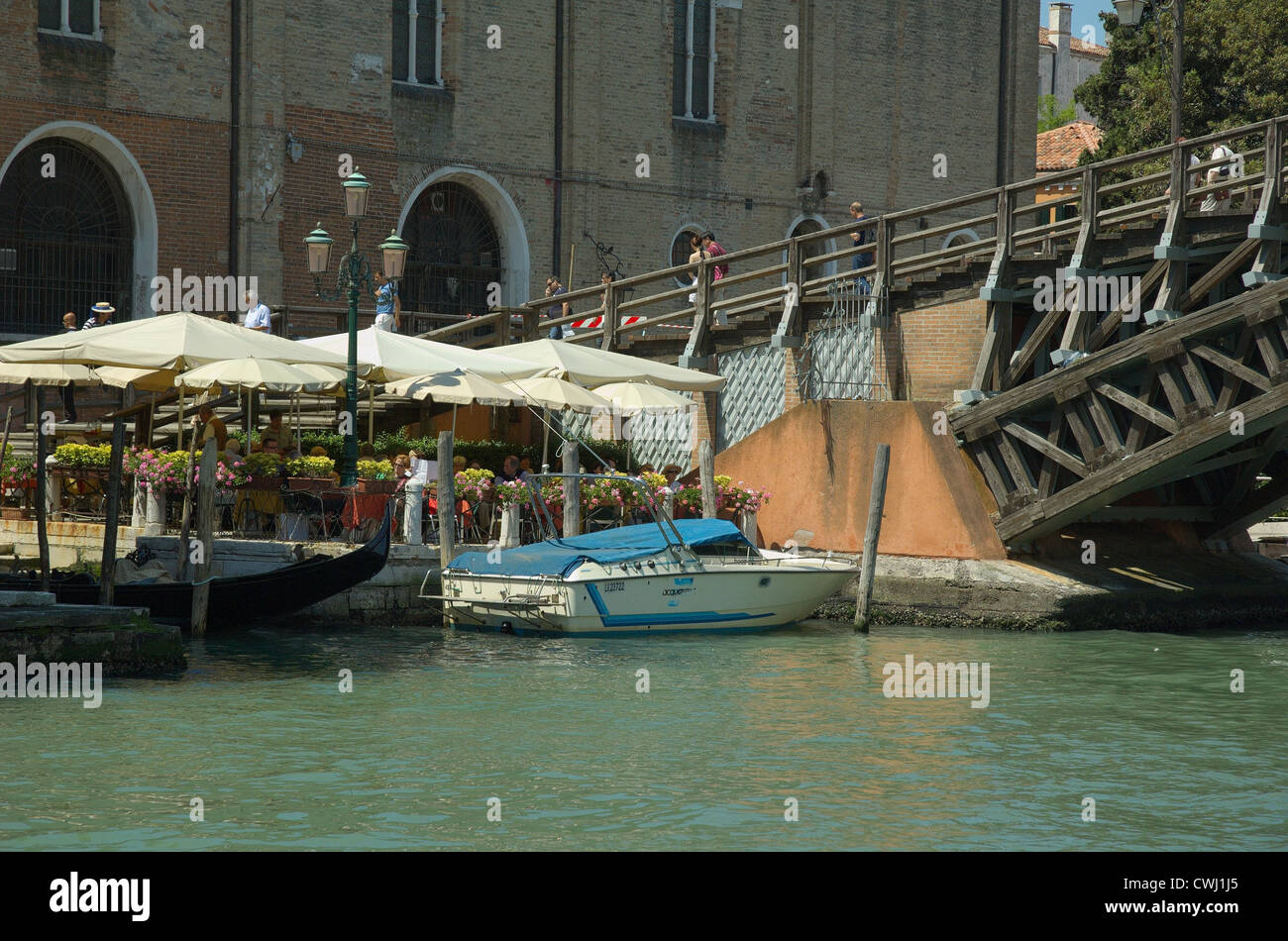 A restaurant at the base of Accademia bridge, Canal Grande, Venice. - Stock Image
