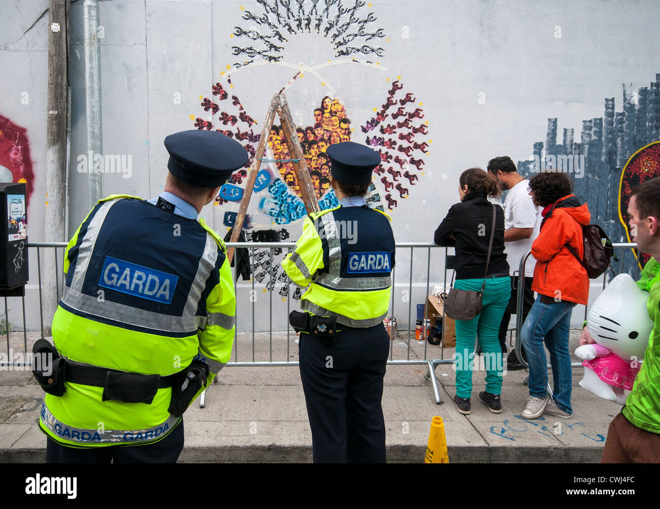 The Garda watching a stencil graffiti artist at work on Hanover Quay in Dublin - Stock Image