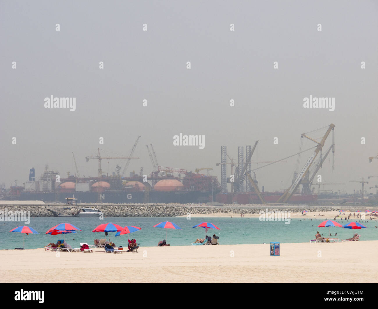 Sunbathers on a beach in Dubai with an industrial site in the background - Stock Image