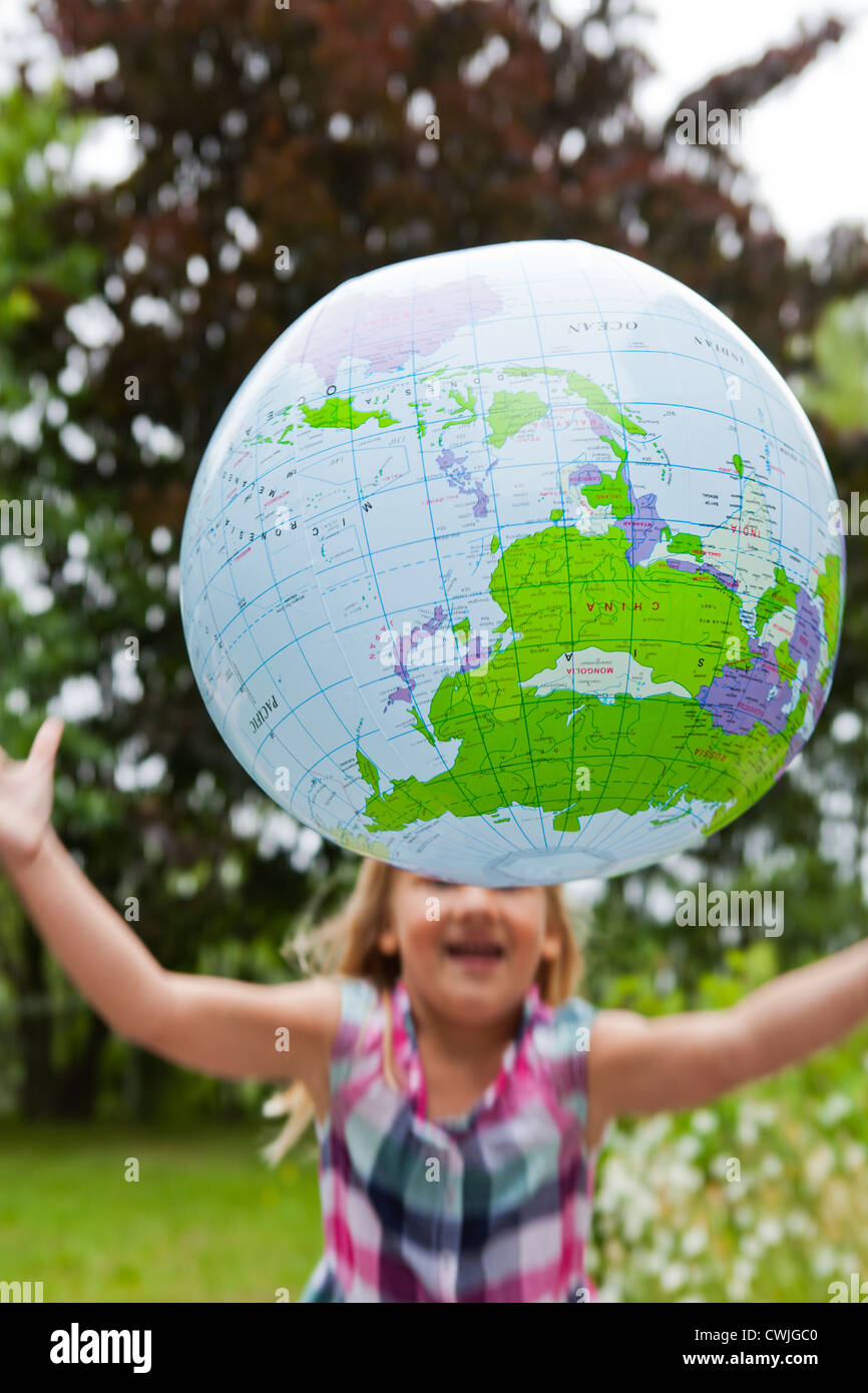 Little girl throwing an earth globe high in the air. Motion blur. - Stock Image