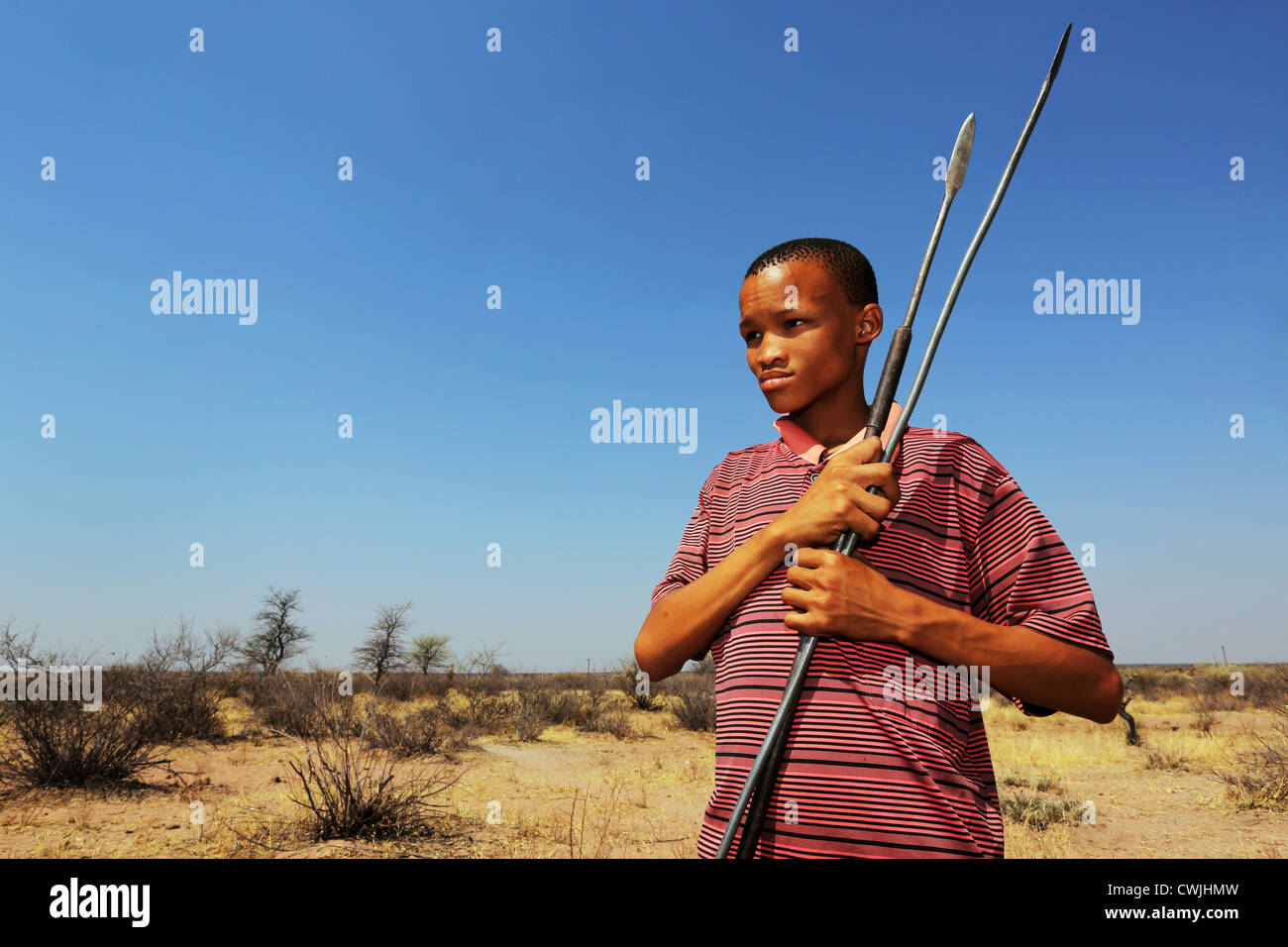Boy of the indigenous San tribe with spears, Namibia, Kalahari desert - Stock Image