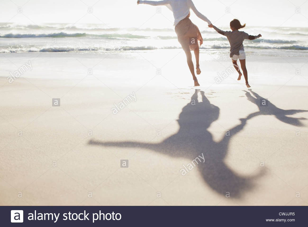 Mother and daughter holding hands and running on sunny beach - Stock Image