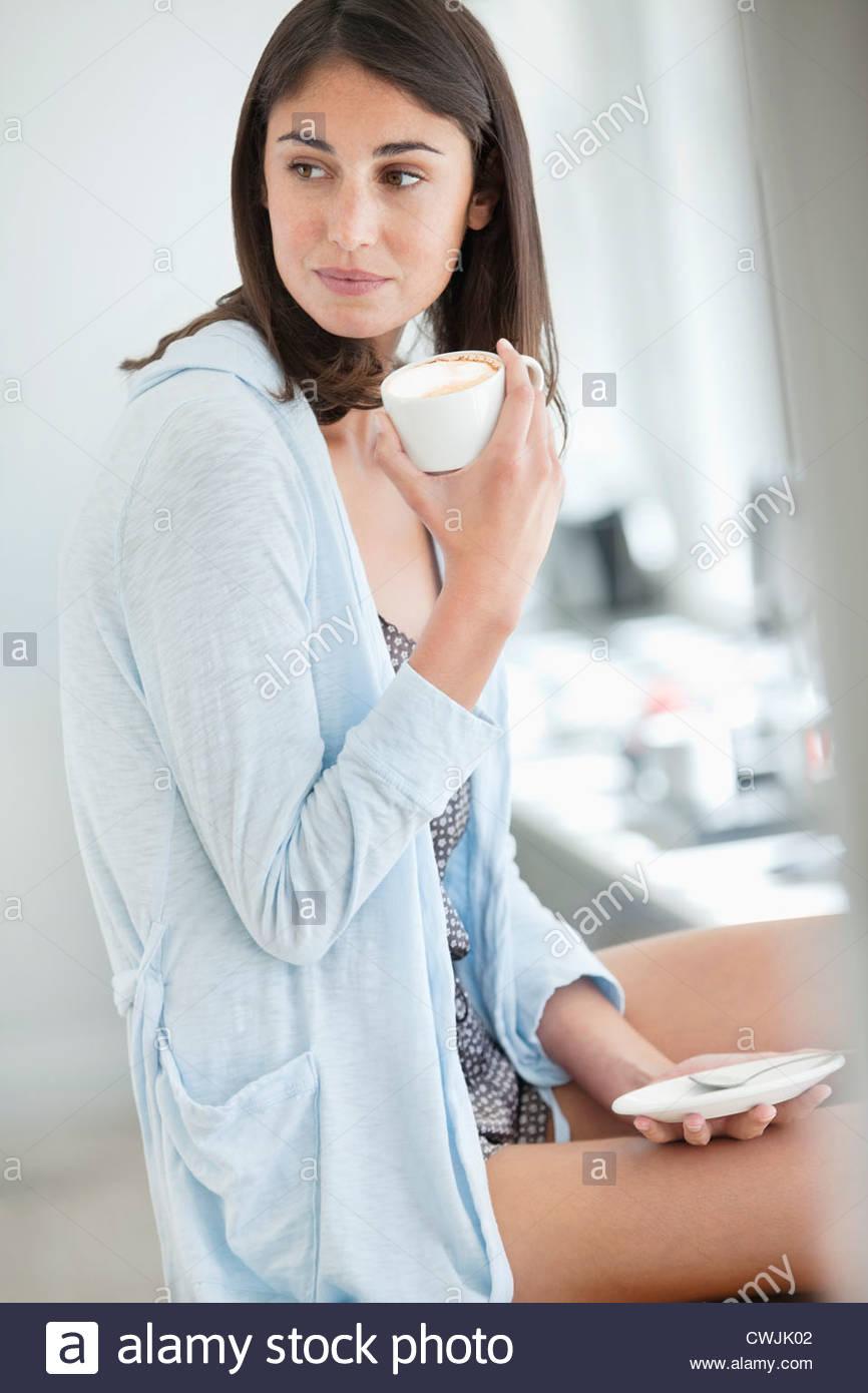 Woman drinking coffee in pajamas - Stock Image