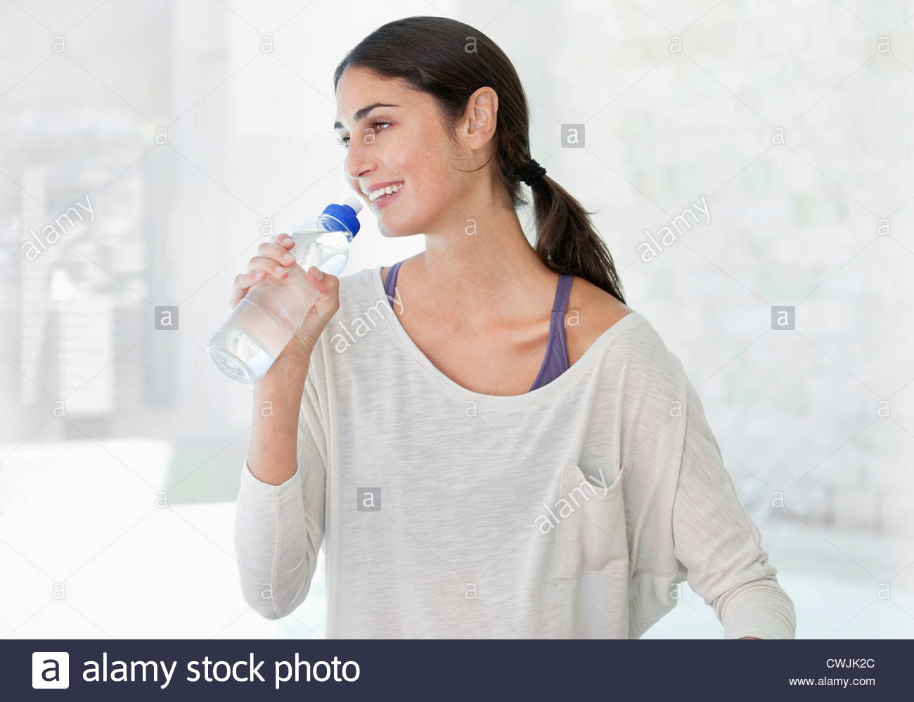 Smiling woman drinking from water bottle - Stock Image