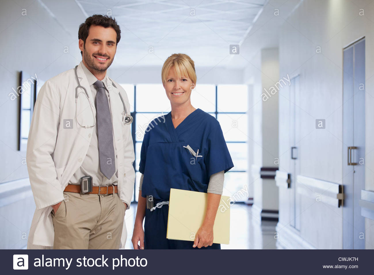 Portrait of smiling doctor and nurse in hospital corridor Stock Photo