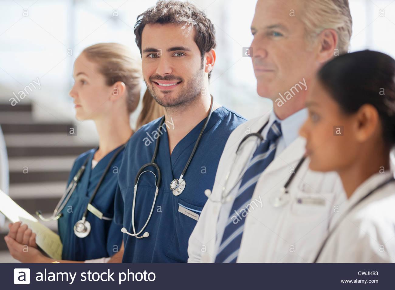 Portrait of smiling nurse with doctors - Stock Image