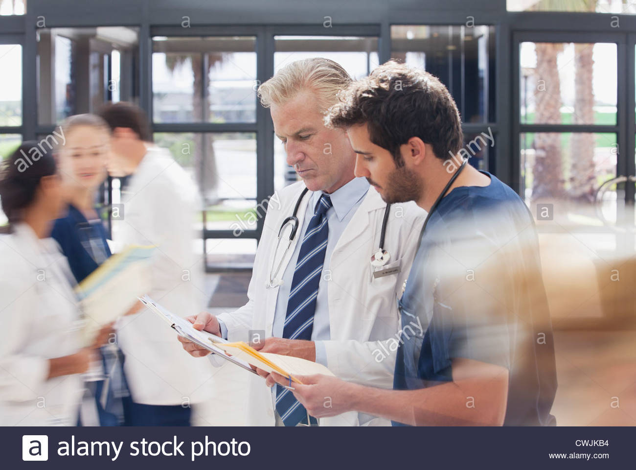 Doctor and nurse reviewing medical record in hospital - Stock Image