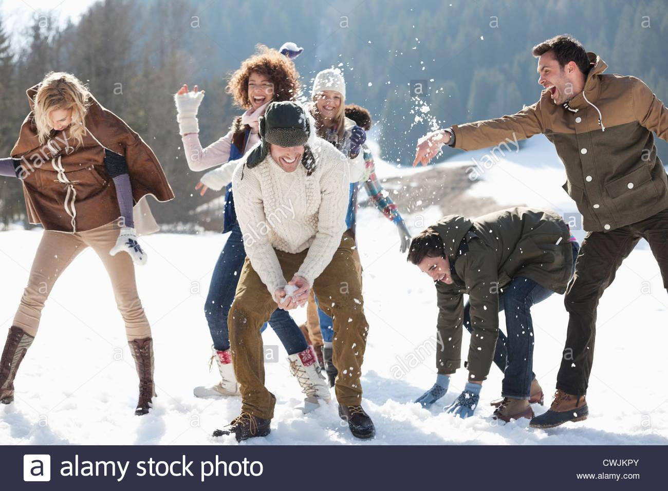 Friends enjoying snowball fight in field - Stock Image