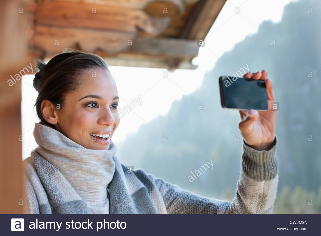 Smiling woman taking photograph with camera phone - Stock Image