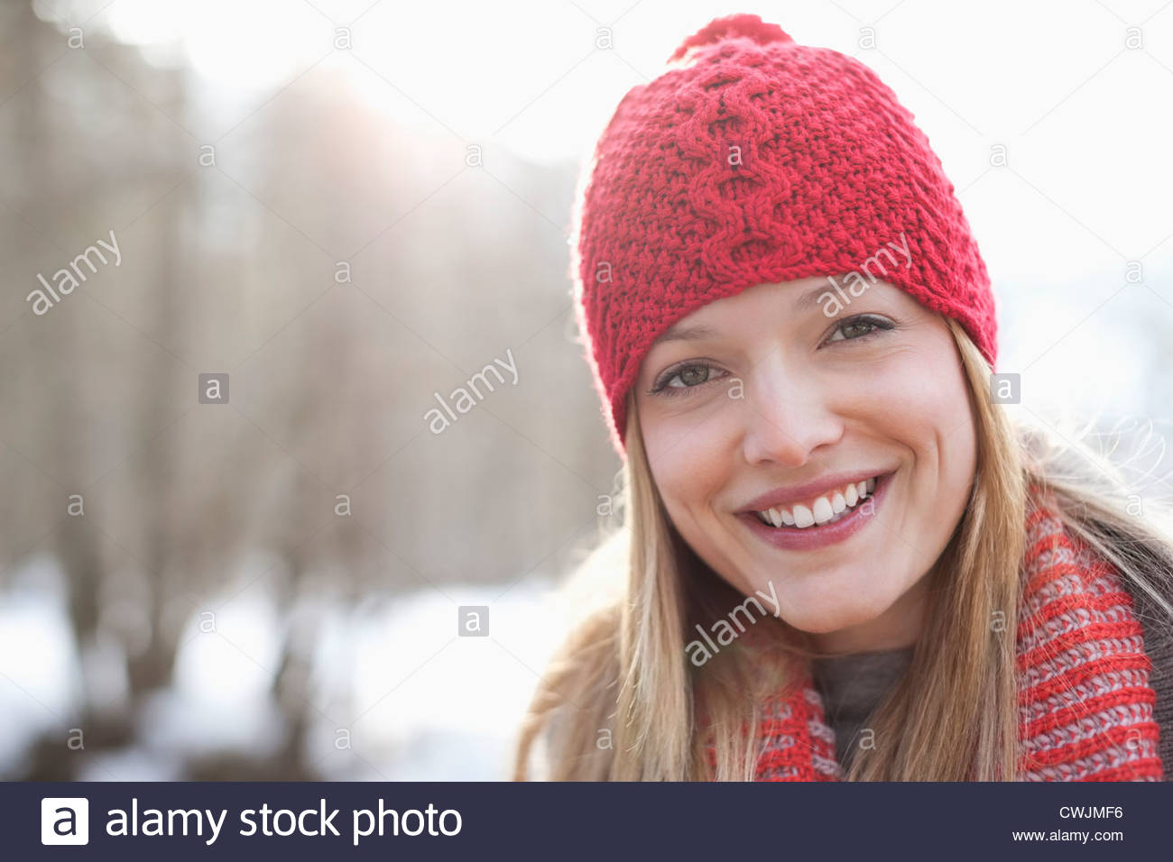 Close up portrait of smiling woman wearing red knit hat - Stock Image
